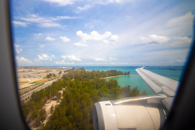 View of the tropical ocean coast from the porthole of a landing plane. holiday travel
