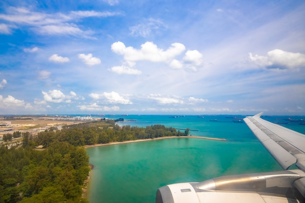 View of the tropical ocean coast from the porthole of a landing plane