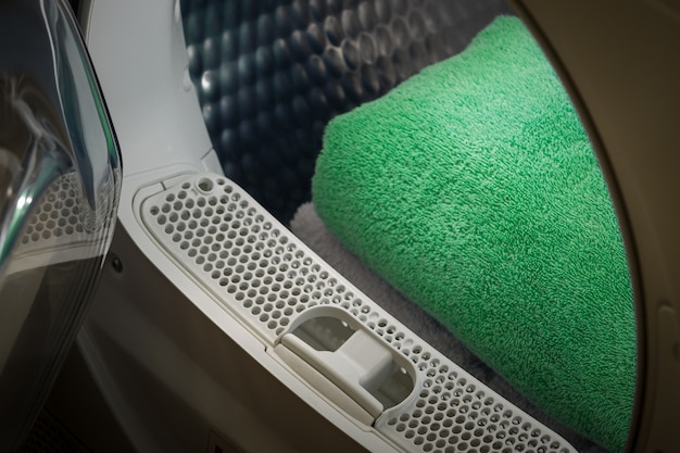 View of the tumble dryer or washing machine with the door open and a green towel inside