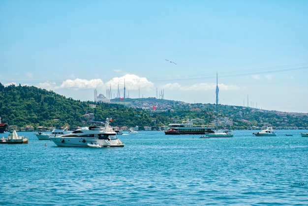 A view of the turkish nature, the boats and the bosporus from an embankment in the arnavutky district of istanbul. turkish san francisco. a mosque in the distance.