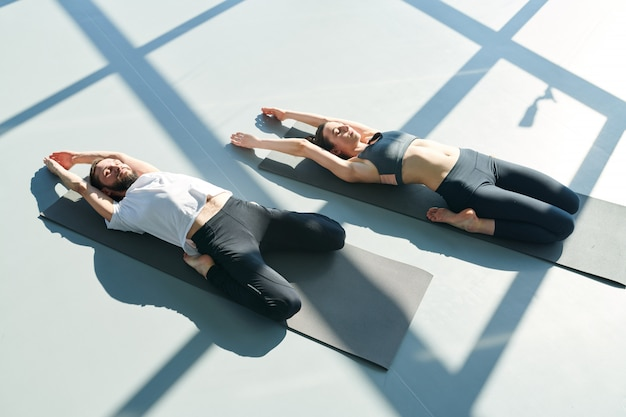 View of two active sportspersons lying on mats with their arms stretched along while practicing relaxing yoga exercise