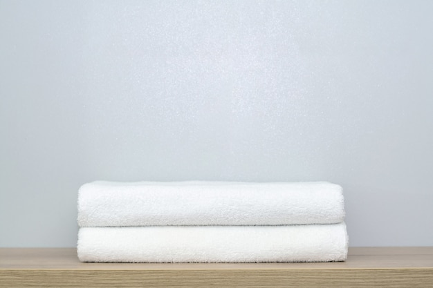 A view of two neatly folded white bath towels on a wooden shelf.