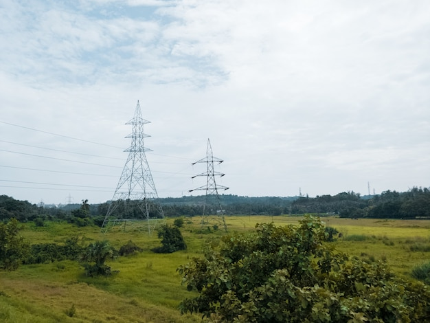 View of two powerline towers standing on a green meadow on a gloomy day background