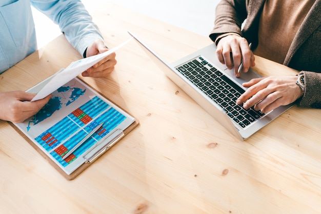 View of two young contemporary financial analysts sitting by wooden table and working with online data and papers