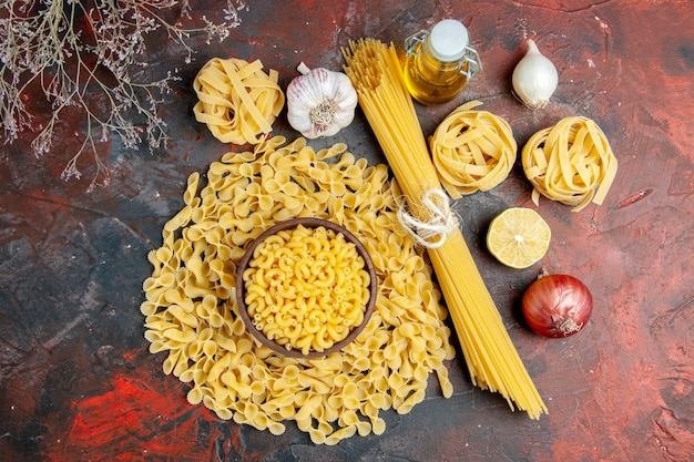 Above view of uncooked pastas in various forms, garlic and onion oil bottle on mixed color table