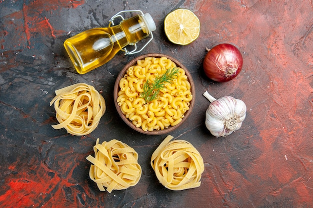 Above view of uncooked three portions of spaghettiand butterfly pastas in a brown bowl and green onion lemon garlic oil bottle on mixed color table