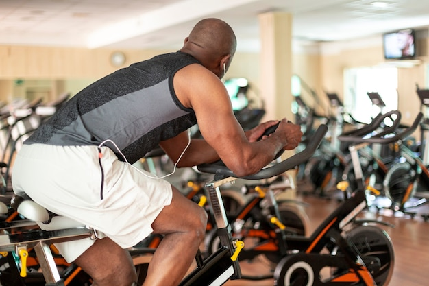 View of unrecognizable black person doing exercise bike in fitness center. healthy lifestyle concept.