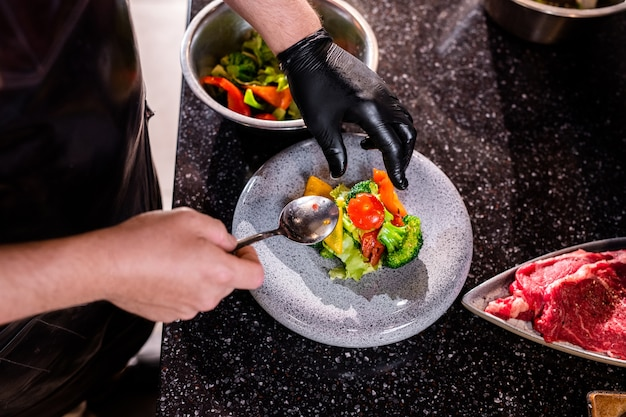Above view of unrecognizable chef in latex glove putting food on plate while preparing dish for restaurant guest