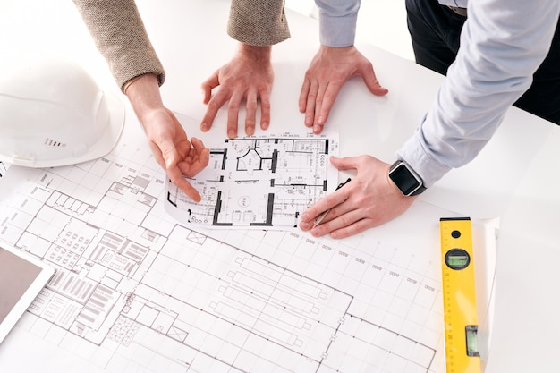 Above view of unrecognizable entrepreneur pointing at flat plan while discussing it with architect