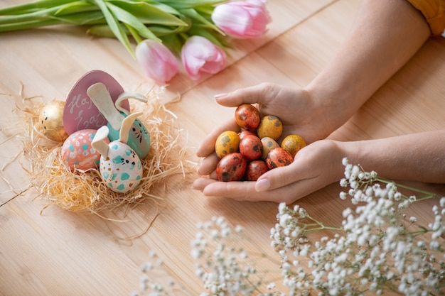 Above view of unrecognizable woman holding handful of quails eggs at wooden table while preparing easter eggs for decorations
