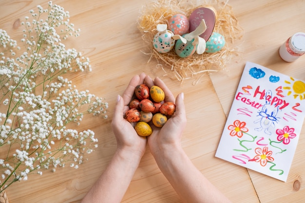 Above view of unrecognizable woman holding painted quails eggs above wooden table with easter card and babys breath
