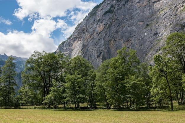 스위스, 유럽, 라우터브루넨(lauterbrunnen) 시의 국립공원에 있는 폭포의 계곡을 보십시오. 여름 풍경, 햇살 날씨, 극적인 푸른 하늘과 화창한 날