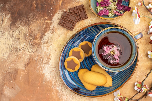 Above view of various biscuits a cup of tea and flowers chocolate bars on mixed color table