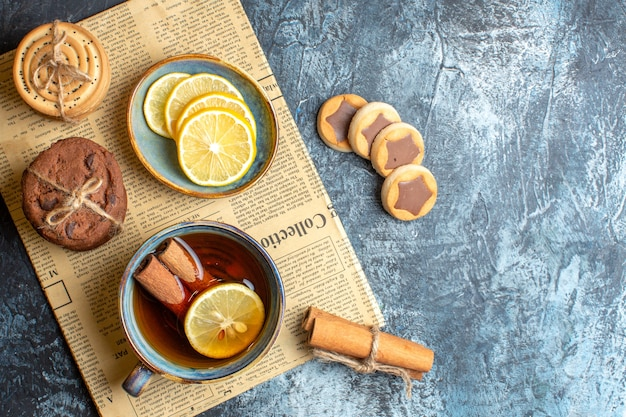 Above view of various cookies and a cup of black tea with cinnamon on an old newspaper on dark background