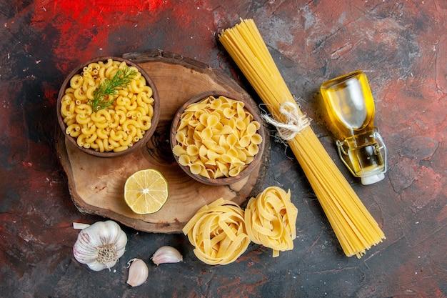 Sopra la vista di vari tipi di pasta cruda e bottiglia di olio di limone e aglio sulla tavola di colori misti