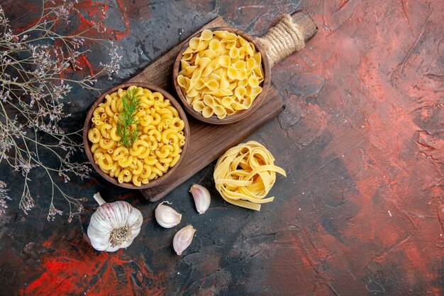 Above view of various types of uncooked pastas on wooden cutting board and garlic on mixed color table