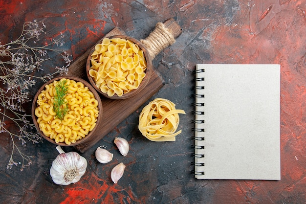 Above view of various types of uncooked pastas on wooden cutting board garlic and notebook on mixed color table