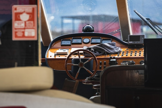 View of the varnished wooden steering wheel of a marine yacht, control devices, gauges, buttons and direction arrows