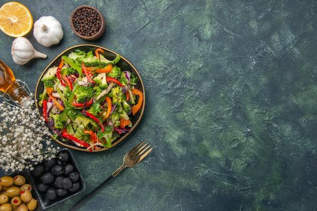 Sopra la vista di insalata vegana in un piatto e forchetta all'aglio fiore bianco caduto bottiglia di olio oliva su sfondo scuro