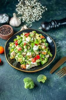 Sopra l'insalata di verdure vista è composta da cetriolo formaggio e pomodori su sfondo blu scuro