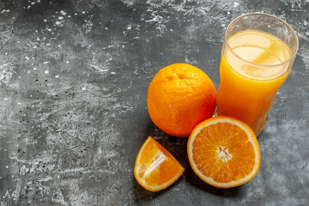 Above view of vitamin source cut and whole fresh oranges and juice on gray background