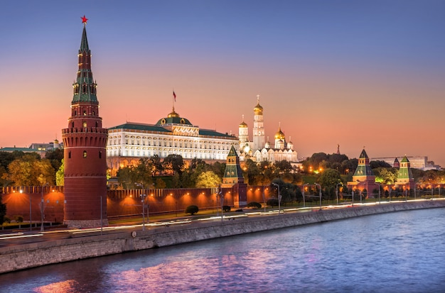 View of vodovzvodnaya, other towers and temples of the moscow kremlin under a pink sunset sky
