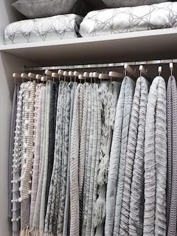 View of a wardrobe with woolen blankets hanging on hangers and pillows and blankets on the shelves.