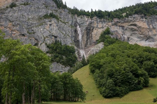 シュタウプバッハの滝、スイス、ヨーロッパのラウターブルンネン市の滝の谷をご覧ください。夏の風景、太陽の光の天気、劇的な空と晴れた日