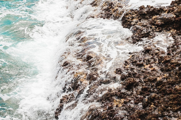 Above view waves at rocky shore