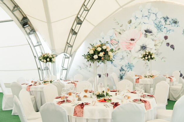 View of the wedding hall, the tent, wedding tables decorated with fresh flowers