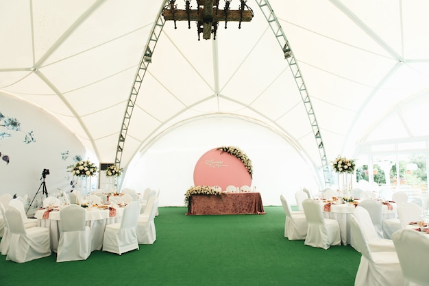 View of the wedding hall, wedding tables decorated with fresh flowers