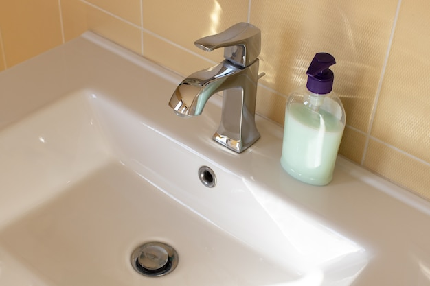 View of a white bathroom sink with a contemporary mixer tap, an unlabeled bottle of liquid soap. concept of modern interior, water saving, everyday hygiene. side view, close-up. horizontal format.