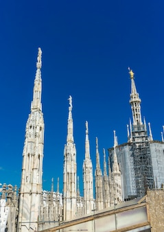 View at white marble statues on the roof of famous cathedral duomo di milano in italy