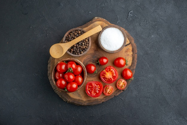 Above view of whole cut fresh tomatoes and pepper on wooden board on black surface with free space