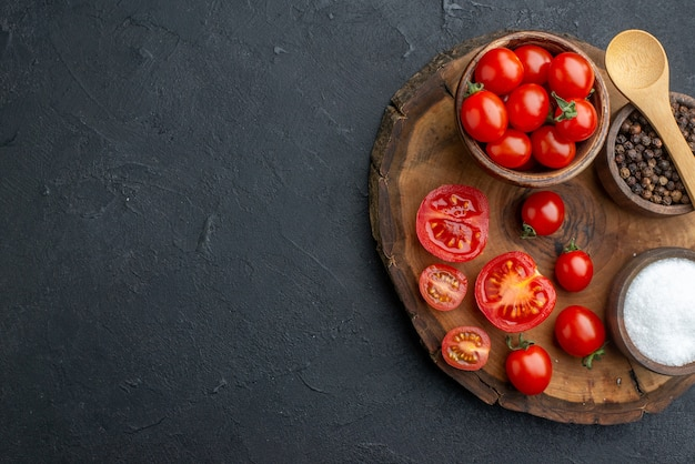 Above view of whole cut fresh tomatoes and spices on wooden board on the left side on black surface with free space