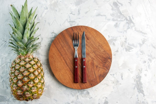 Above view of whole fresh golden pineapple fork knife on cutting board on marble surface