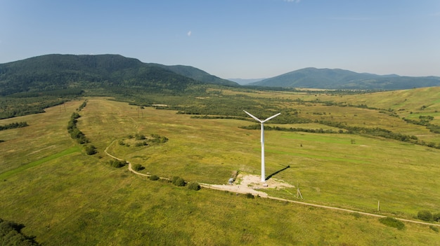 View of wind turbine with mountains in the background. alternative energy.