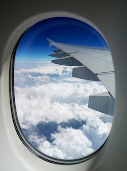 View of the wing of a passenger plane from the porthole in the sky