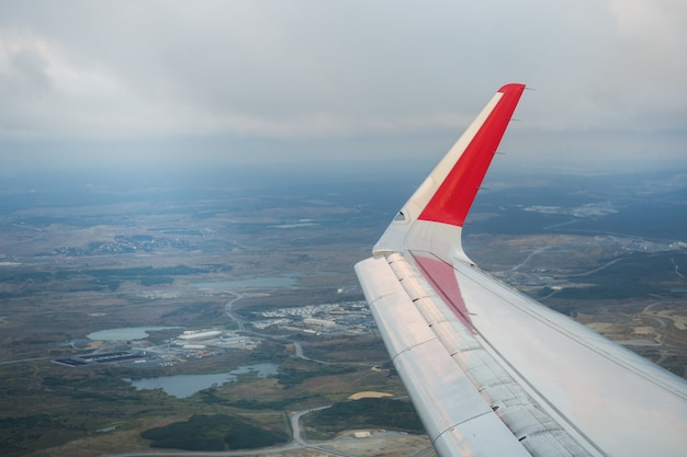 View the wing of the passenger plane and the ground from the window of the flying aircraft.