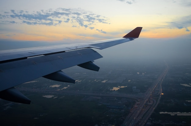 View of the wing of the plane and the city and the road in the morning at dawn.