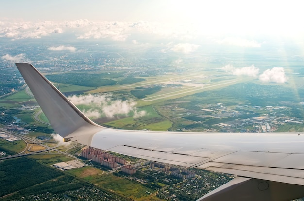 View of the wing of the plane in the porthole on the city and the airport with picturesque clouds