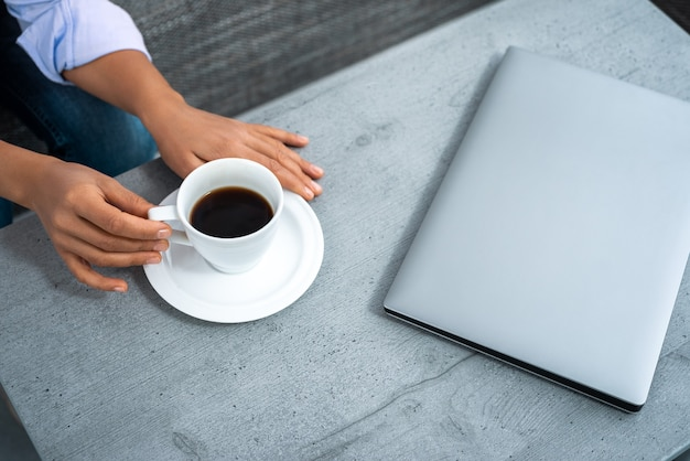 The view of the woman's  hands reaching for a cup of coffee on the table. near a laptop.