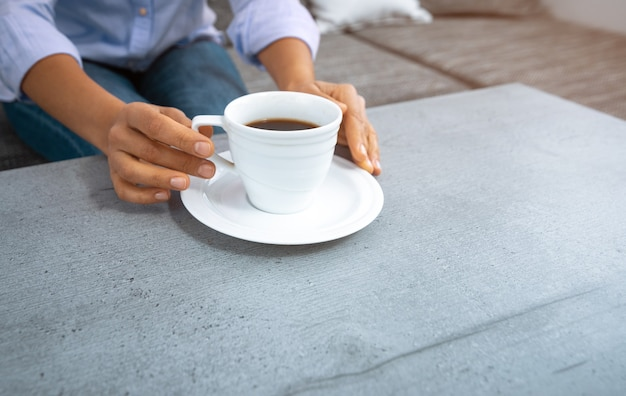 The view of the woman's  hands reaching for a cup of coffee on the table.