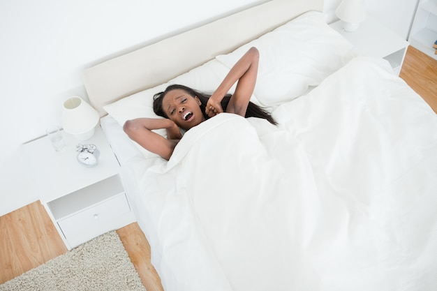 Above view of a woman yawning and stretching her arms while waking up