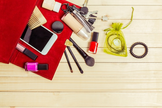View on women bag stuff on wooden background