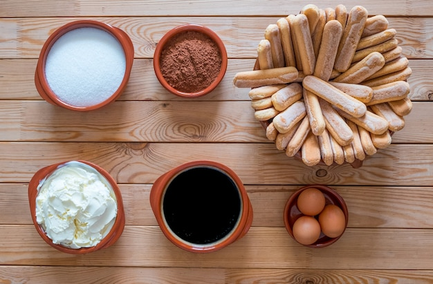 Above view of a wooden table with ingredients to prepare a homemade tiramisu