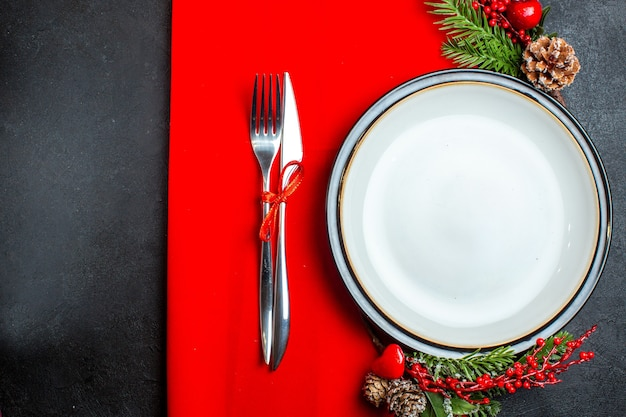 Above view of xsmas background with dinner plate decoration accessories fir branches and cutlery set on a red napkin