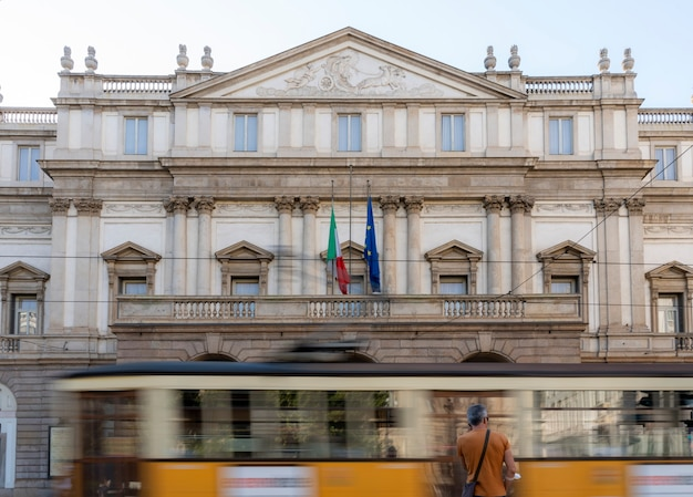 View of the yellow tram passing in front of theater in milan, italy