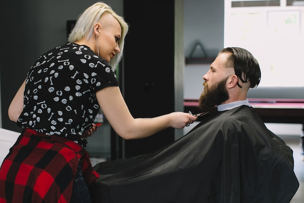 View of young bearded man getting beard haircut by hairdresser at barbershop.