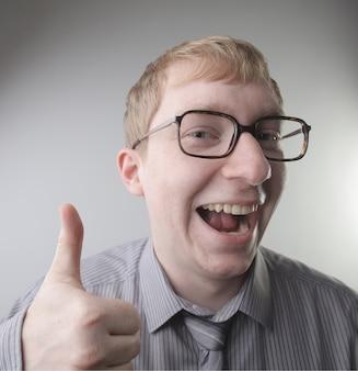 Vista di un giovane maschio caucasico che indossa una camicia e cravatta con impressioni faccia felice - concetto: felice